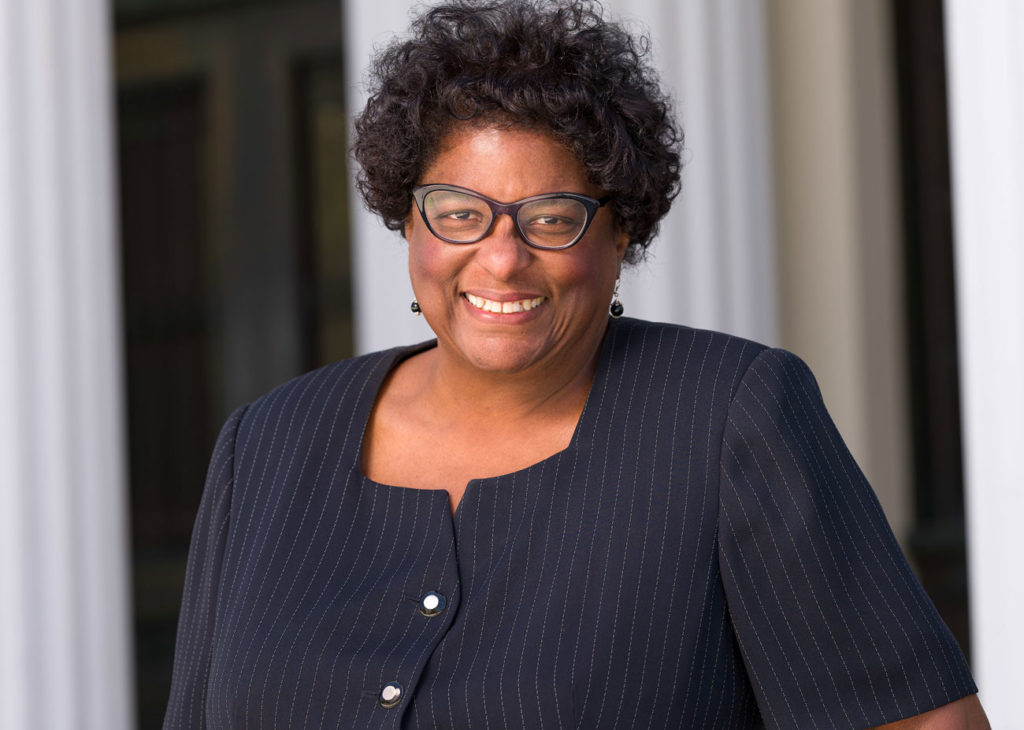 An African American woman in a navy pinstripe suit, dangly earrings, and sharp black glasses. smiles at the camera.
