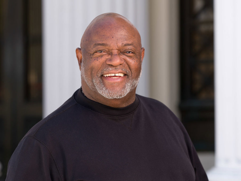 A bald African American man wearing a black shirt looks at the camera. He has white whiskers and is smiling.