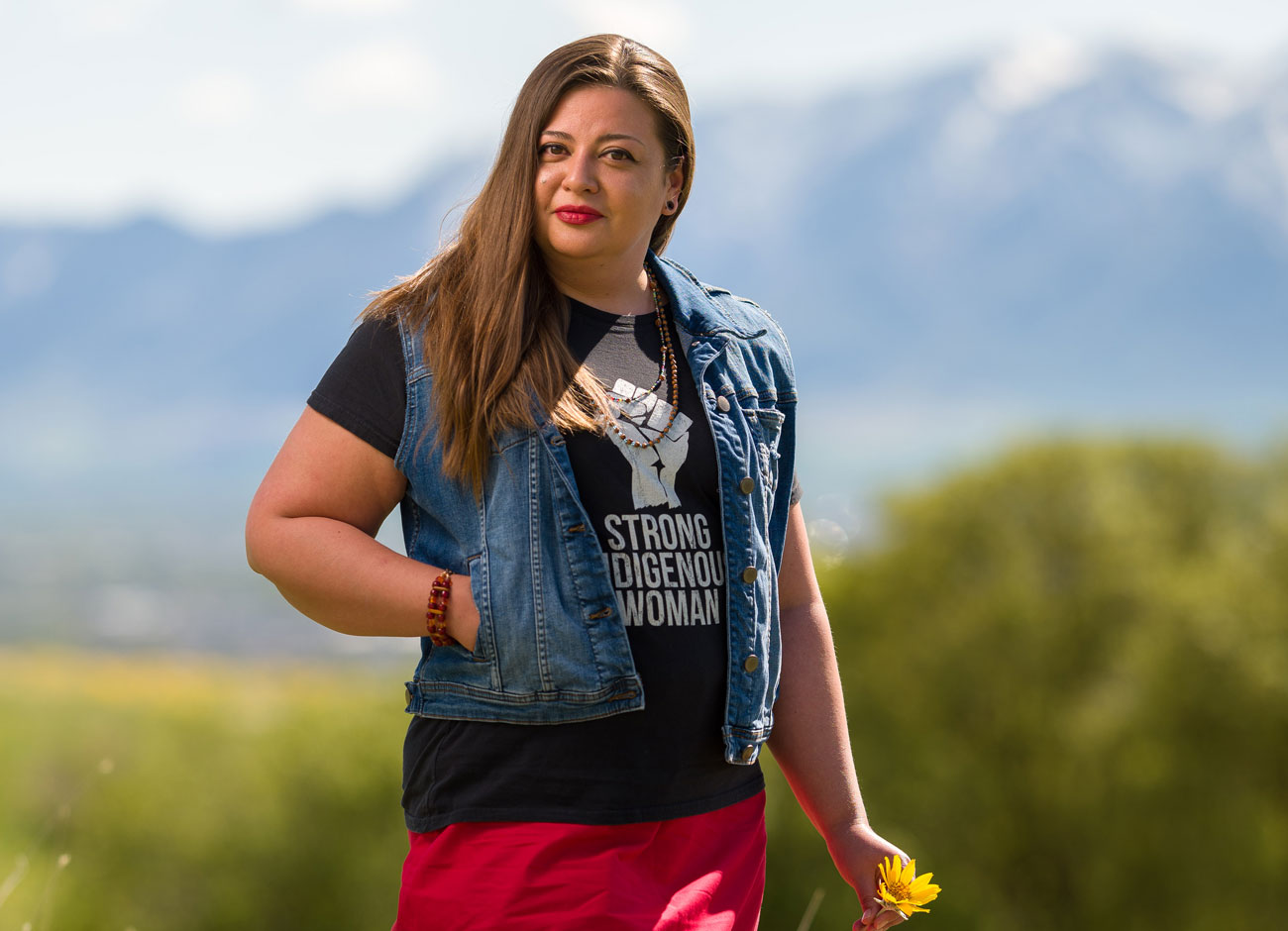 """a young Native American woman wearing a """"strong Indigenous woman"""" t-shirt and red dress with colored strips on the bottom stands in a field of bright golden flowers. She has a knowing smile."""